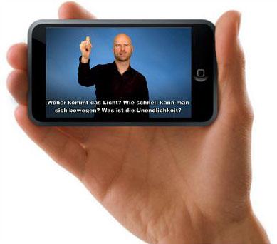 Foto iPhone in der Hand. Auf dem iPhone läuft ein Video mit einem gebärdenden Kulturvermittler und ist untertitelt.