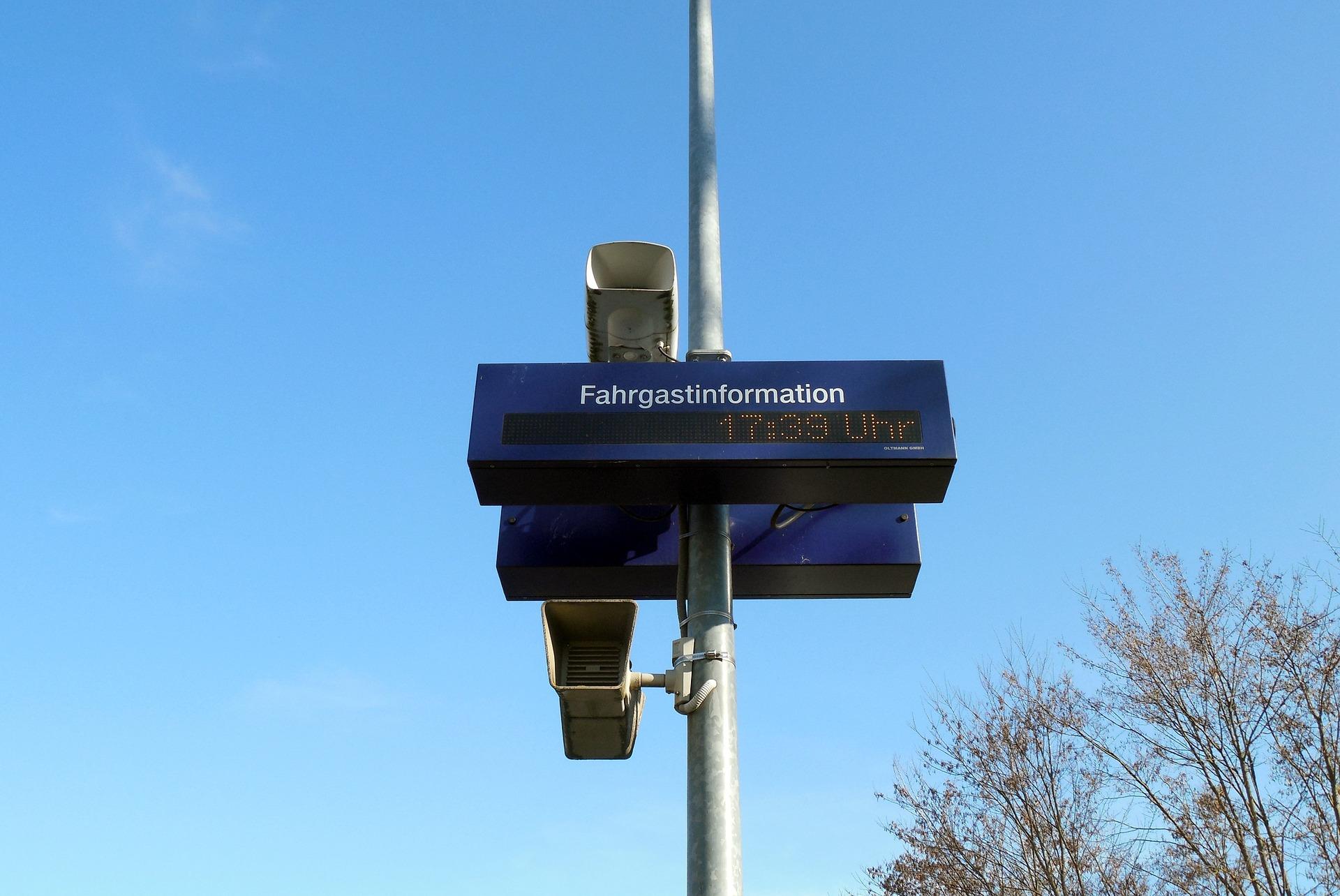 Foto von einer Einzeilen Fahrgastinformation-Anzeige und daneben vier Lautsprecher montiert.