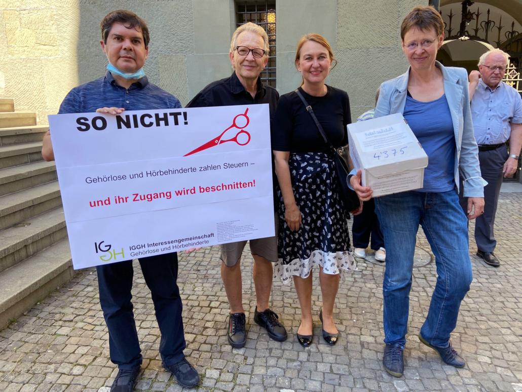 Plakat: So nicht! Gehörlose und Hörbehinderte zahlen Steuern - und ihr Zugang wird beschnitten. Von links: Victor Senn, Beat Ledermann, Brigitte Schökle und Yvonne Brütsch